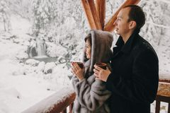 Stylish couple holding hot tea in cups and looking at winter snowy mountains from wooden porch. Happy romantic family with drinks royalty free stock photography