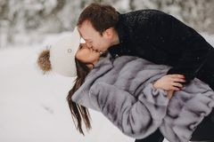 Free Stylish Couple In Love Gently Kissing In Snowy Mountains. Portra Stock Photo - 129663150