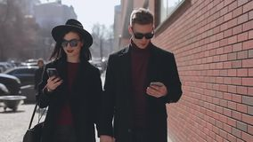 Stylish couple looking down into their smartphones walking along city street stock video footage