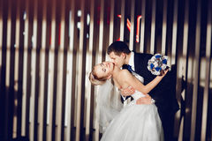 Stylish couple in love the bride and groom are dancing, kissing and cuddling in the modern and stylish interior of the restaurant Stock Image