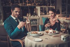 Stylish couple with mobile phones in a restaurant Stock Photos