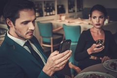 Stylish couple with mobile phones in a restaurant Stock Image