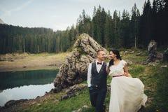 Happy couple of newlyweds against the backdrop of the mountains. Stylish couple of newlyweds against the backdrop of the mountains in Italy royalty free stock photo
