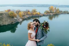 Stylish couple newlyweds smile and hugging standing before a lake. Bride and groom with dreadlocks look at each other Stock Photography