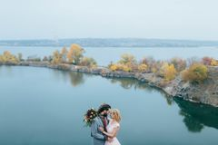 Stylish couple newlyweds smile and hugging standing before a lake. Bride and groom with dreadlocks look at each other Royalty Free Stock Image