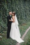 Stylish couple of newlyweds on their wedding day. Happy young bride, elegant groom and wedding bouquet royalty free stock images