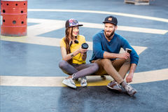 Stylish couple with skateboard outdoors stock images