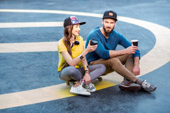 Stylish couple with skateboard outdoors stock photography