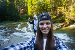 Stylish couple take selfie on camera near river in middle of forest royalty free stock photos