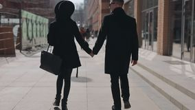 Stylish couple walking along city street holding hands, rear view stock video footage