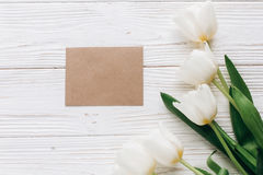 Stylish craft greeting card and tulips on white wooden rustic ba Stock Image