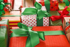 Stylish creative presents in colored paper decorated with red, green satin ribbon bows. Gift wrapping background closeup. Packaging modern christmas present Royalty Free Stock Photos