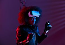 Stylish curly dark haired girl dressed in black leather jacket and gloves is wearing the virtual reality glasses on her royalty free stock image
