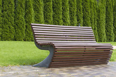 Stylish curve shaped brown wooden bench outdoor furniture in the park as background image Royalty Free Stock Photography