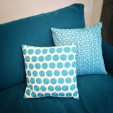 Stylish cushions decorating blue sofa Stock Images