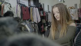 Stylish customer girl choosing basic pieces of clothing for her autumn winter wardrobe in a mall store -. Stylish customer girl choosing basic pieces of clothing stock footage