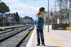 Cute boy at the train station waiting for the train. Stylish cute boy at the train station waiting for the train in summer Royalty Free Stock Photo