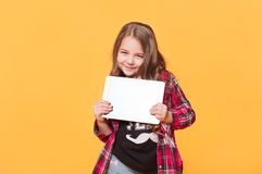 Stylish Cute Child with tablet computer. Little happy girl wearing casual modern clothes showing blank white screen  on yellow background Stock Image