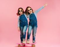 Stylish cute girls with skateboard. And wearing fashion clothes on pink background. Happy children with skateboard enjoying together stock photo