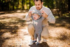 Dad picks up by hands his laughing son outdoors. Stylish dad picks up by hands his laughing son in a funny gray suit and blue boots Stock Photography