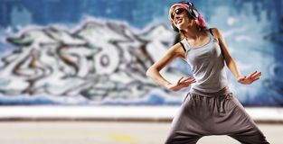 Stylish dancing girl against abstract wall Stock Photo