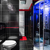 Stylish dark bathroom. With simple white toilet and fancy shower with hydromassage stock photography