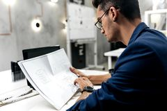 Stylish dark-haired architect in glasses and in a blue jacket is working with documents on the desk in the office stock images