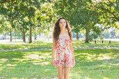 Stylish day dreaming brunette walking on grass Stock Photo