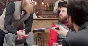 Stylish designers sharing new ideas and insights about business. Casual meeting in a coffee shop. Bearded man checking paperwork stock video footage