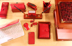 Stylish desktop for business lady. Computer, mobile phone, paper tray and stationery in red color scheme Royalty Free Stock Images