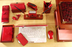 Stylish desktop for business lady. Computer, mobile phone, paper tray and stationery in red color scheme Royalty Free Stock Photo