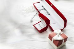 Stylish diamond ring in red present box and luxury jewelry accessories on white rustic wooden background. happy valentine day car. D concept. greeting flat lay royalty free stock image