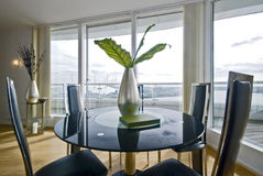 Stylish dining area with round glass top table. Stylish dining area with black round glass top table, leather chairs for four and floor to ceiling windows with Royalty Free Stock Image