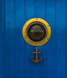 Stylish door with a bull`s eye and an anchor-shaped knocker, an Royalty Free Stock Photo
