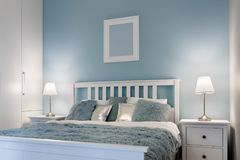 Stylish double bed. In pastel colored bedroom Royalty Free Stock Images