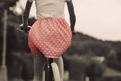 Stylish dressed girl rides on an old bicycle with a retro effect Royalty Free Stock Images