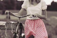 Stylish dressed girl rides on an old bicycle with a retro effect Stock Images