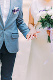Stylish dressed groom holding hand of his lovely bride, Wedding couple walks on garden background Royalty Free Stock Photos