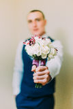 Stylish dressed man holding elegant bouquet indoor. Focus on flowers with blurred person image Royalty Free Stock Photo
