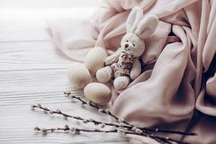 stylish easter bunny rabit and eggs and willow buds on rustic wooden background and fabric . greeting card concept with space for royalty free stock photo