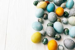 Stylish Easter eggs border on white wooden background, copy space. Modern easter eggs painted with natural dye in yellow,blue, royalty free stock photo