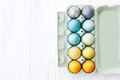 Stylish Easter eggs in carton tray on white wooden background, space for text. Modern colorful easter eggs painted with pastel stock photos