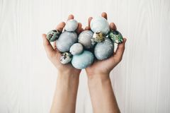Stylish easter eggs in female hands on white wooden background. Hands holding modern easter eggs painted with natural dye in grey. And blue marble color. Happy stock photo