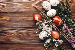 Stylish easter eggs with white flowers and buds on wooden background flat lay. modern eggs and natural dyed with herbs, willow b. Uds top view. space for text stock images