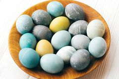 Stylish Easter eggs on wooden plate on white wooden background. Modern easter eggs painted with natural dye in yellow,blue,green, stock photo