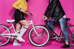Stylish elderly couple in leather jackets riding bicycles together Royalty Free Stock Images