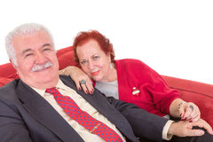 Stylish elderly couple sitting on a red sofa Stock Image