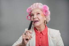 Stylish elderly female with hair rollers crooning into brush Royalty Free Stock Photo
