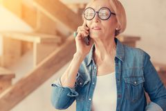 Stylish elderly woman talking on phone. Stay in touch. Stylish aged woman resting at home and talking on her cell phone Royalty Free Stock Photography