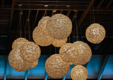 Stylish electrical lanterns spheres hanging out from dark brown ceiling Stock Photo